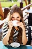 Café potable de jeune femme dans un café dehors Image stock