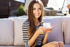 Café potable de jeune femme dans un café dehors Images stock