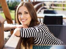 Café potable de jeune femme dans un café dehors Photo stock