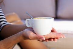 Café potable de jeune femme dans un café dehors Photographie stock libre de droits