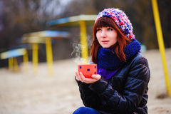 Café potable de jeune femme de son thermos, appréciant la soirée d'automne par la mer Image stock