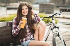 Café potable de jeune femme en voyage de bicyclette Photographie stock libre de droits