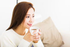 Café potable de jeune femme et se reposer sur le sofa photographie stock libre de droits