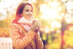 Café potable de jeune femme heureuse en parc d'automne Photos stock