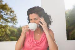 Café potable de jeune femme tout en parlant au téléphone portable Images stock