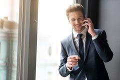Café potable de jeune homme gai tout en ayant la conversation sur le smartphone photo stock