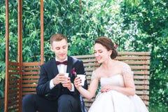 Café potable de jeunes beaux jeunes mariés au café d'extérieur Jour du mariage heureux Photographie stock libre de droits