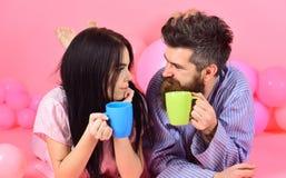 Café potable de jeunes couples dans le lit, fond rose Les couples détendent dans le matin avec Couples en café de boissons d'amou Photos libres de droits