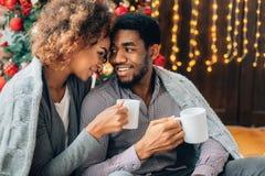 Café potable de jeunes couples et apprécier le matin de Noël photos libres de droits