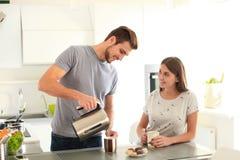 Café potable de jeunes couples mignons dans la cuisine Photo libre de droits