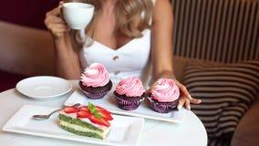 Café potable de jolie dame élégante avec les desserts savoureux banque de vidéos