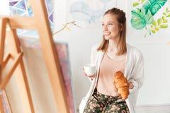 Café potable de peintre heureux de dame mangeant le croissant Images stock