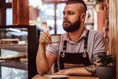 Café potable de port de tablier de barman beau pendant la pause de midi se reposant à une table dans le café photo libre de droits