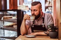 Café potable de port de tablier de barman beau pendant la pause de midi se reposant à une table dans le café photographie stock libre de droits