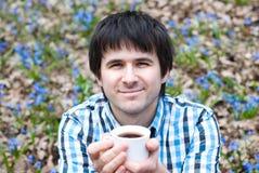 Café potable de sourire d'homme dans la forêt Photographie stock