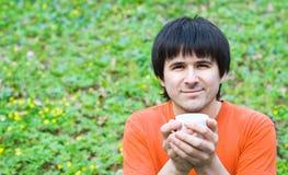 Café potable de sourire d'homme sur la nature. photographie stock