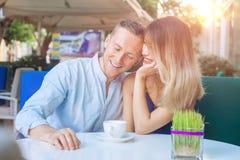 Café potable de sourire de couples multiculturels heureux Photographie stock libre de droits