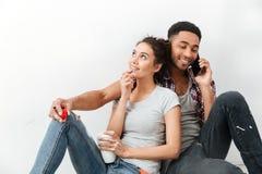 Café potable de sourire de jeunes couples et parler au téléphone portable Images stock