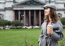 Café potable de sourire de jeune femme élégante tout en marchant sur une rue de ville photographie stock