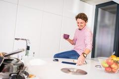 Café potable de sourire de jeune homme dans la cuisine images libres de droits