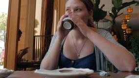 Café potable ou thé de jeune fille tenant la tasse blanche dans des mains et regardant à la fenêtre se reposant dans la zone de s clips vidéos