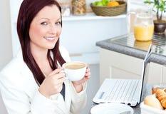 Café potable rougeoyant et sourire de femme d'affaires Photo libre de droits