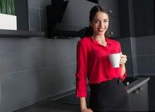 Café potable/thé de belle femme d'affaires dans une cuisine moderne photos stock
