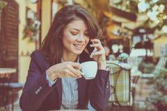 Café potable un bavardage avec l'ami au téléphone Image stock