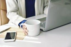 Café pour le rafraîchissement, femme d'affaires travaillant sur l'ordinateur portable photos stock