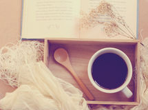 Café preto e colher na bandeja de madeira com livro, filtro retro Foto de Stock
