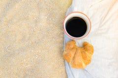 Café preto e croissant no fundo da areia, no café da manhã na praia, no alimento e no conceito da bebida foto de stock royalty free