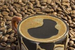Café preto em um copo entre feijões de café Fotografia de Stock Royalty Free