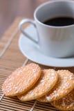 Café preto no copo branco e em biscoitos friáveis do arroz com em woode Imagem de Stock Royalty Free