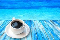 Café preto no copo em uma tabela de madeira e em um mar bonito fotos de stock