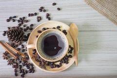 Café preto quente no copo de madeira e em feijões de madeira da colher e de café imagem de stock royalty free