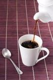 Café que derrama dentro à caneca Fotos de Stock Royalty Free