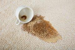 Café que desborda la taza en la alfombra fotos de archivo