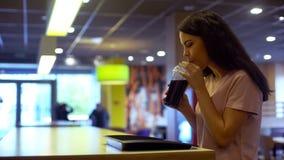 Café que se sienta de goce femenino joven del refresco, cóctel de consumición de la mujer sedienta fotografía de archivo libre de regalías