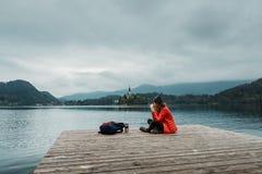 Café que se sienta y de consumición de la mujer joven del backpacker por el lago de la montaña Foto de archivo libre de regalías