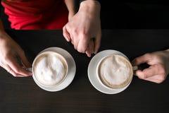 Café que se sienta y de consumición de los pares jovenes en el restaurante del café dos tazas con café están en la tabla Manos de Imagen de archivo libre de regalías
