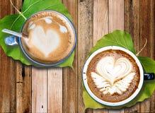 Café quente com arte da espuma do leite com as folhas sob canecas, na mesa de madeira velha Imagem de Stock Royalty Free