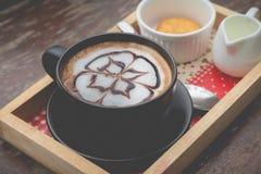 Café quente com arte do leite da espuma Xícara de café preta Foto de Stock