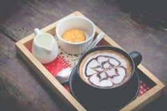 Café quente com arte do leite da espuma Xícara de café preta Fotos de Stock Royalty Free