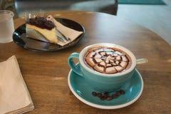 Café quente com bolo de queijo do mirtilo no copo e em uns pires verdes Imagens de Stock Royalty Free