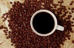 Café quente com os feijões na textura de madeira Imagem de Stock