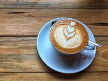 Café quente do cappuccino no copo e nos pires brancos com a colher no fundo de madeira da tabela Arte do desenho da espuma do lei fotos de stock