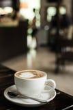 Café quente do Latte da arte em um copo na tabela e na cafetaria de madeira bl Foto de Stock