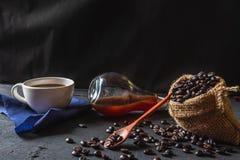 Café quente e feijões de café crus em um fundo preto fotos de stock royalty free