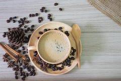Café quente em feijões de madeira do copo e de café fotografia de stock royalty free