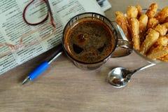 Café quente em um vidro em um bom dia e em um jornal de manhã Imagens de Stock